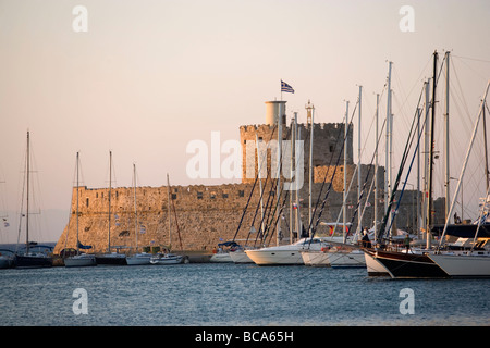 View along anchoring ships at mole with fortress tower Agios Nikolaos in background, Mandraki harbour (translated - Stock Photo