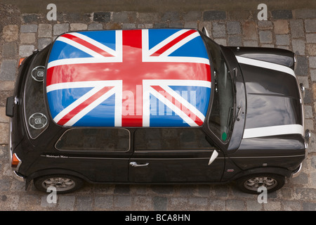 Europe Union Jack painted on roof of a black Mini car from above - Stock Photo