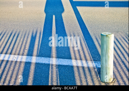 long shadows of a pair of legs and fence on asphalt - Stock Photo