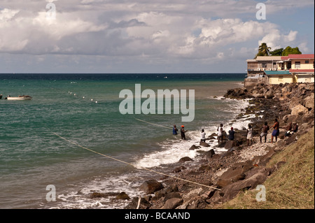 Locals at Gouyave village hauling in a fishing net on the beach - Stock Photo