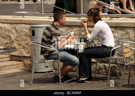 Young couple enjoying a café style lunch snack in the short British summer - Stock Photo