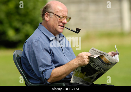 middle-aged man reading local newspaper at local cricket match - Stock Photo