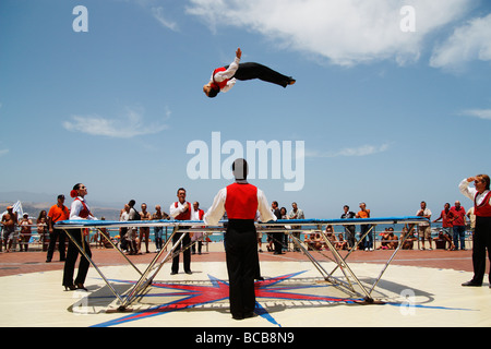 Circus act performing outdoors on trampolIne near beach in Spain - Stock Photo
