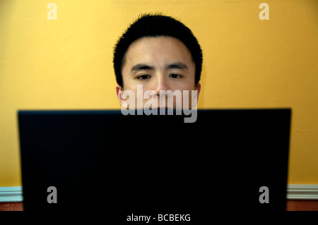 Young Chinese Student in France, Portrait Looking at Laptop Computer Screen at Home alone, man face Frontal