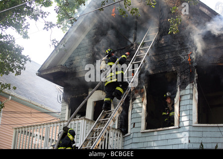 Firefighters climb a ladder during a battle a two alarm blaze in New Haven Connecticut USA - Stock Photo