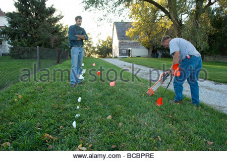 A plumber uses an electronic probe to locate a leaking water line. - Stock Photo