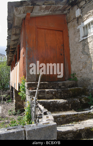 Peeling orange paint on back door at country farm in Spain - Stock Photo