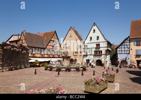 Street scene in Place du Chateau square in picturesque medieval village on the wine route. Eguisheim Haut-Rhin Alsace - Stock Photo