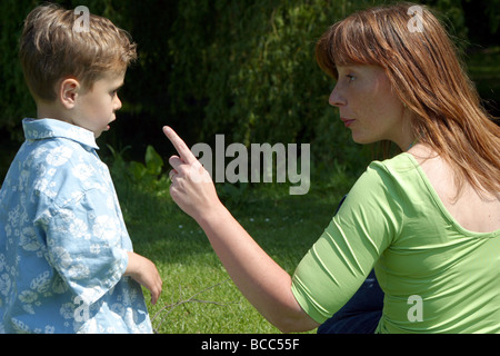 Rebellion little boy told off by his overprotective mother outside, she is warning and pointing at her toddler son - Stock Photo