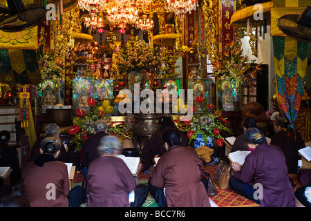 Women praying in the temple located next to One Pillar Pagoda inside the Ho Chi Minh Mausoleum Complex in Hanoi - Stock Photo