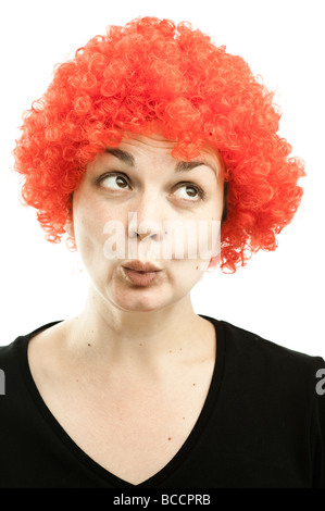 a woman wearing a cheap curly red clown's wig - Stock Photo