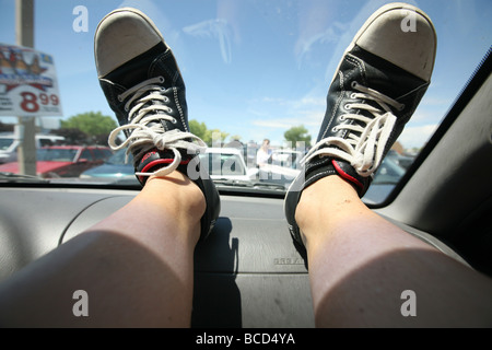 Human feet lying on car dashboard at 4th of July parade - Stock Photo