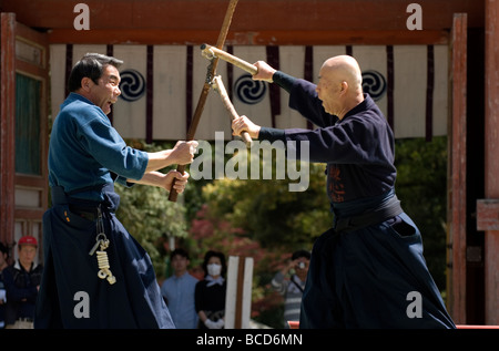 Two men engage in a heated fight using traditional Japanese weapons such as nunchaku and wooden stick - Stock Photo