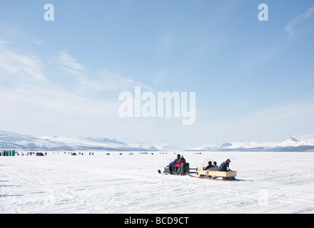 Vain kaksi kalaa ( Only two fish ) ice fishing competition competitors and snowmobile at Lake Kilpisjärvi  Lapland - Stock Photo