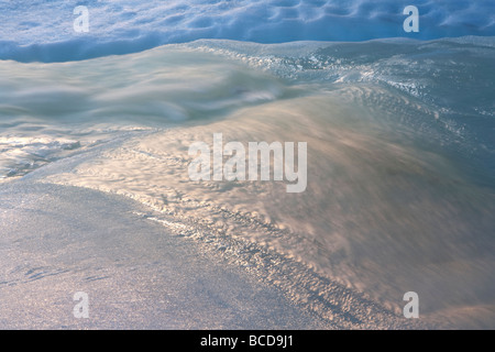 Stream of water flowing on ice cover at Norwegian Lapland at wintertime - Stock Photo