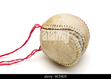 Old worn baseball with red thread seams pulled out and loose leather cover - Stock Photo