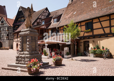 War memorial and half-timbered buildings in medieval village square on the wine route. Eguisheim Alsace France. - Stock Photo