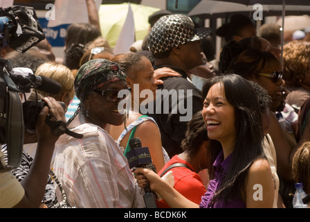 A reporter interviews a fan outside the Apollo Theater in Harlem in New York during a memorial to Michael Jackson - Stock Photo