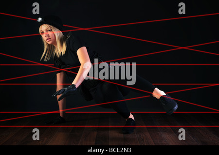 Blond cat burglar climbing through a laser beam alarm system - Stock Photo