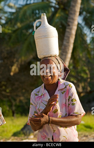 Mozambique, Inhaca Island. An african lady on the Island of Inhaca in Mozambique carrying home made wine. - Stock Photo