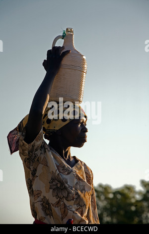 Mozambique, Inhaca Island. An african lady on the Island of Inhaca in Mocambique carrying a jug of home made wine. - Stock Photo