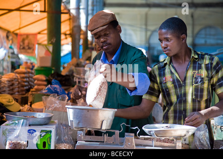 Mozambique, Maputo. A stall holder weighs his produce with the help of his assistant in the Central Market. - Stock Photo