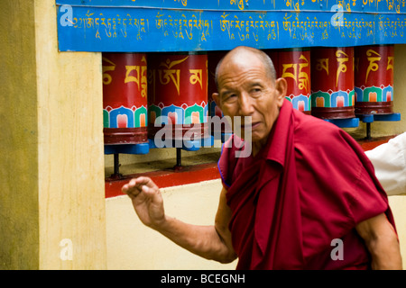 Old buddhist Tibetan monk turns prayer wheels on Kora path around Tsuglagkhang Complex. McCleod Ganj. Himachal Pradesh. - Stock Photo