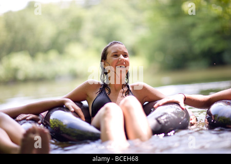 Teenagers sitting in innertubes in the water - Stock Photo