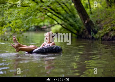 Teenage girl floating in an innertube in the water - Stock Photo