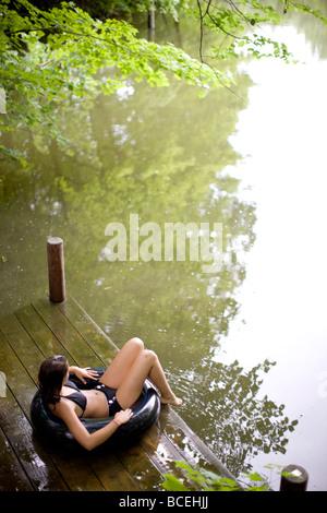 Teenage girl sitting in an innertube on the edge of a dock - Stock Photo