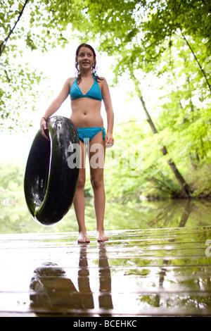Teenage girl wearing a bathing suit holds an innertube - Stock Photo