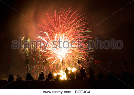 A group of people watch fireworks light up the sky at a fiesta. - Stock Photo