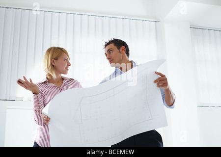 female and male architects holding blueprint - Stock Photo