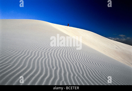 A distant hiker crests a pure white sand dune in the late afternoon. - Stock Photo