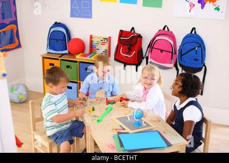 Four kids playing in preschool classroom - Stock Photo