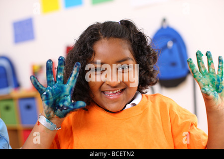 Preschool girl with hands covered in paint - Stock Photo