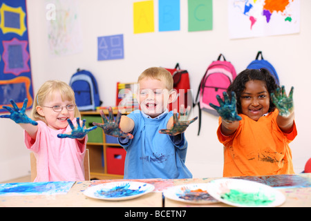 Three preschool kids with hands covered in paint - Stock Photo