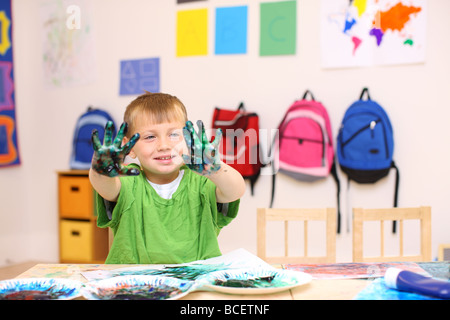 Preschool boy holding up hands covered in paint - Stock Photo
