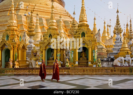 Myanmar, Burma, Yangon. Two Buddhist monks pass the small stupas, temples and shrines at the Shwedagon Golden Temple - Stock Photo