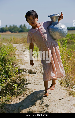 Myanmar, Burma, Rakhine State, Laung Shein. A young girl from Laung Shein village collects water from a nearby dam. - Stock Photo