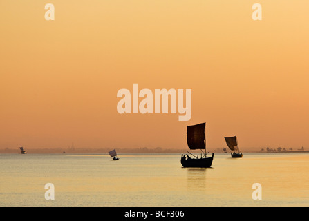 Myanmar, Burma, Rakhine State, Kaladan River. A golden sunset on the Kaladan River as sailing boats head for home. - Stock Photo