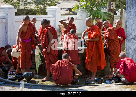 Myanmar, Burma, Rakhine State, Sittwe. Young novice monks wash their utensils at a well at Pathain Monastery. - Stock Photo
