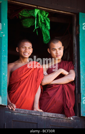 Myanmar, Burma, Rakhine State, Sittwe. Two novice monks look out of their dormitory window at the Pathain Monastery. - Stock Photo