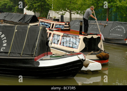 Boatman mopping cabin roof of traditional working narrowboat amongst a basin full of Fellows, Morton & Clayton boats, - Stock Photo