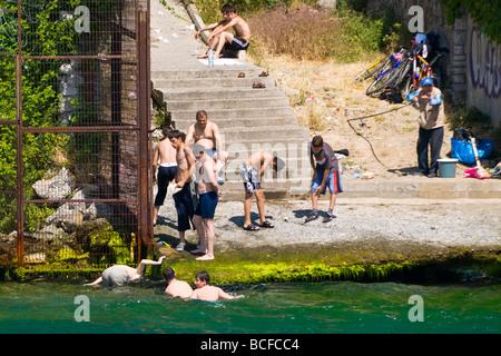 Turkey , Istanbul , Bosphorous or Bogazi , Kuzguncuk , young boys & men in trousers & shorts bathe enjoy water front - Stock Photo