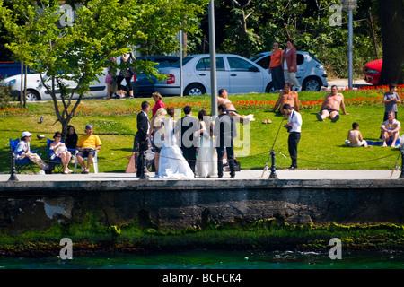 Turkey , Istanbul , Bosphorous or Bogazi , Kuzguncuk , bride bridegroom & party pose for photos surrounded by sunbathers - Stock Photo