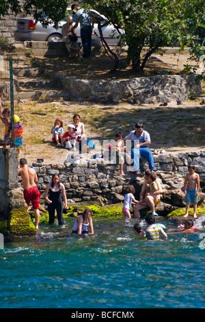 Turkey , Istanbul , Bosphorous or Bogazi , Kuzguncuk , crowd of young people enjoy the water bathing mostly fully - Stock Photo