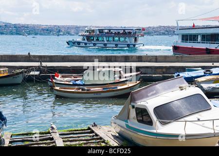 Turkey , Istanbul , Kabatas , Bosphorous or Bogazi , scene of ferry boat sailing past small marina with old boats - Stock Photo