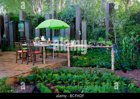 Table and chairs on deck with green umbrella with adjacent work bench for potting - Stock Photo