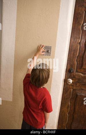 seven year old boy turning off light switch at home to save energy - Stock Photo